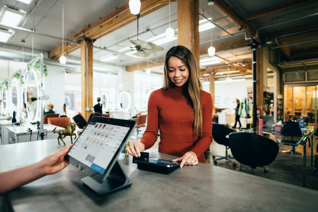A pretty lady swiping her credit card at a retail store's checkout counter.  She is standing near the business' computerized Point of Sale (POS) system.