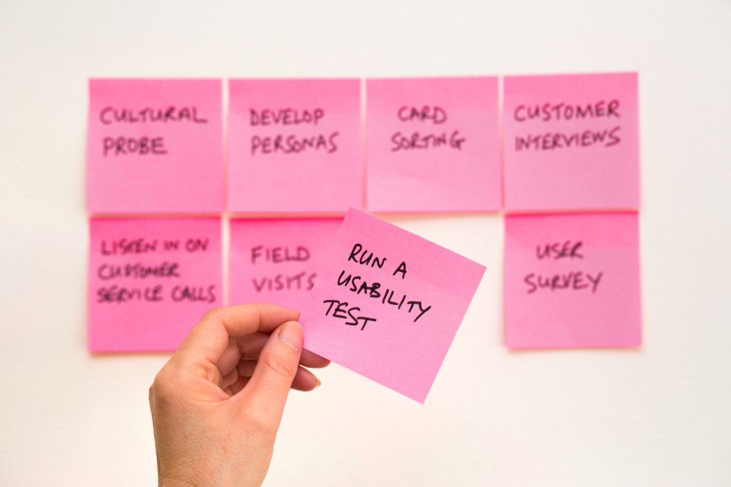 Multiple pink 'sticky notes' showing phrases such as 'Customer Interviews' and 'Run a usability test'.  This in support of researching software that will meet the customer's needs.