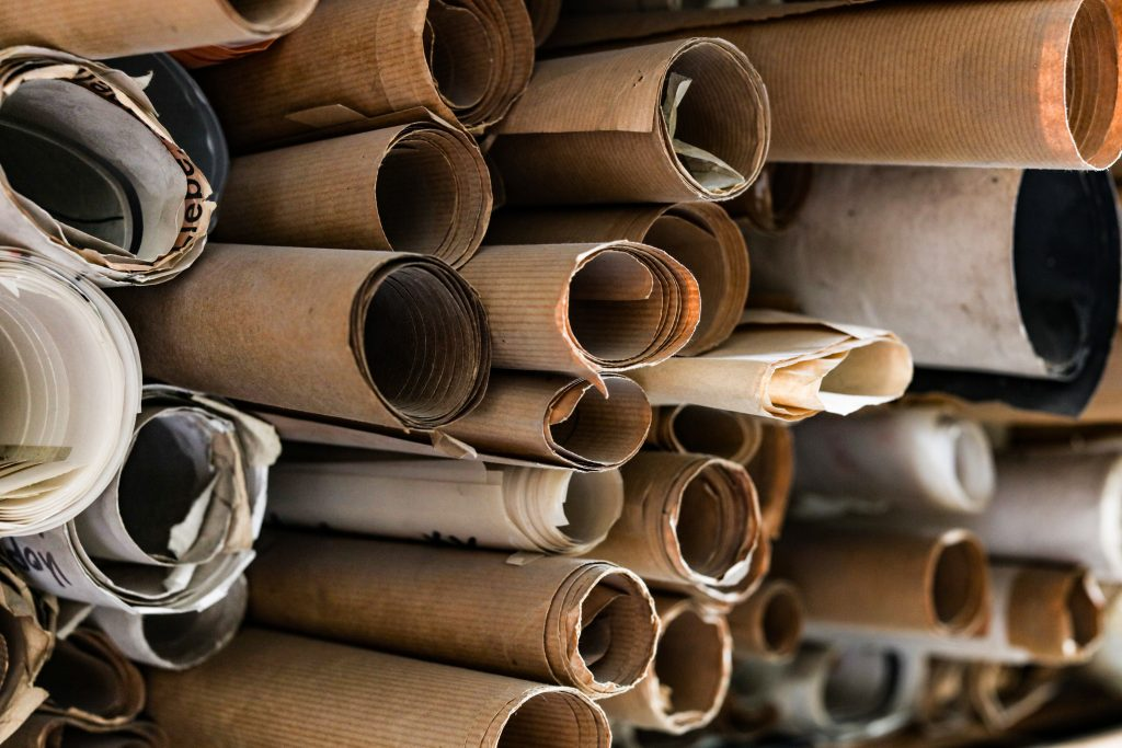 a bunch of rolled up documents that represent 'swimming in paper work' which could be managed by a computer system.